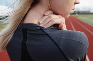 Neck Pain. Athletic fitness woman rubbing the muscles of her back. Sports exercising injury.Pain relief, chiropractic concept